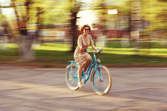 Girl on a bicycle in movement Stock Images