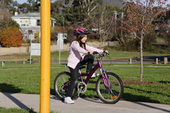 Girl on bicycle at park. A girl on a bicycle waiting to cross the road royalty free stock image