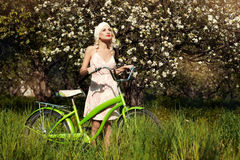 Girl with bicycle in the park. Stock Photography