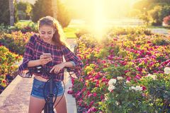 Girl bicycle playing with smartphone in park royalty free stock image