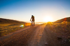 Girl on a bicycle in the rays of the rising sun Royalty Free Stock Photography