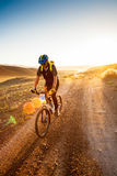 Girl on a bicycle in the rays of the rising sun Royalty Free Stock Image