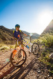 Girl on a bicycle in the rays of the rising sun stock photography
