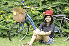 Girl with a bicycle rests on a grass Stock Photography