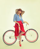 Girl with a bicycle in a retro style. Blonde with bicycle on background Royalty Free Stock Images