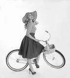 Girl with a bicycle in a retro style. Blonde girl with a bicycle in a retro style on a white background Royalty Free Stock Photography