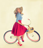 Girl with a bicycle in a retro style. Blonde girl with a bicycle in a retro style on a white background Stock Photography