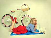 Girl with a bicycle in a retro style. Blonde girl with a bicycle in a retro style on a white background Stock Photo