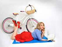 Girl with a bicycle in a retro style. Blonde girl with a bicycle in a retro style on a white background Royalty Free Stock Image
