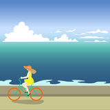 A girl on a bicycle rides along the sea shore. Vector illustration of a sea. Summer sea walk. Cartoon naive drawing. The girl in the hat Stock Images