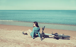 Girl with a bicycle sitting on beach Royalty Free Stock Image