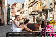 Girl with bicycle sitting on bench and reading book Stock Image