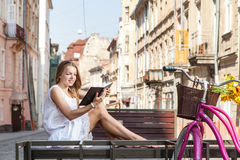 Girl with bicycle sitting on bench and reading book Royalty Free Stock Image