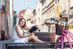 Girl with bicycle sitting on bench and reading book Stock Photo