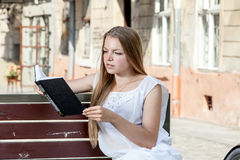 Girl with bicycle sitting on bench and reading book Royalty Free Stock Photography