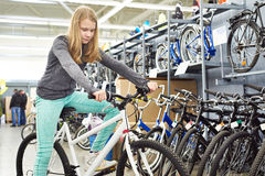 Girl with bicycle in sport shop Royalty Free Stock Photography