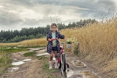 Girl with bicycle stand on the rural road Royalty Free Stock Photo