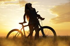 Girl on a bicycle in the sunset. Royalty Free Stock Photography