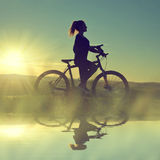 Girl on a bicycle in the sunset. Reflected on the water surface Royalty Free Stock Photo