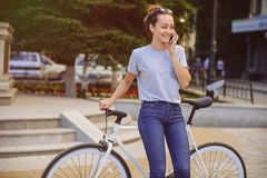Girl with Bicycle talking on the phone. Girl with bike fix on the phone. Concept health sport Stock Photos
