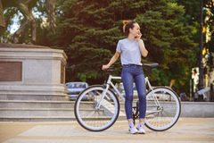 Girl with Bicycle talking on the phone. Girl with bike fix on the phone. Concept health sport Stock Image