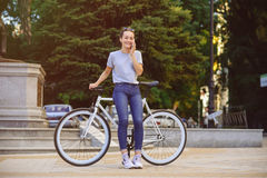 Girl with Bicycle talking on the phone. Girl with bike fix on the phone. Concept health sport Stock Images