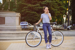 Girl with Bicycle talking on the phone. Girl with bike fix on the phone. Concept health sport Royalty Free Stock Photography