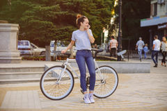 Girl with Bicycle talking on the phone. Girl with bike fix on the phone. Concept health sport Stock Photo