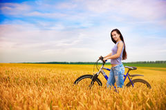 Girl with a bicycle on the wheat field Stock Photography