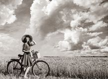 Girl with bicycle on wheat field royalty free stock photography