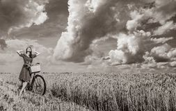 Girl with bicycle on wheat field. royalty free stock images
