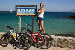 Girl with 2 bicycles against Mediterraneo sign at seaside Spain. Blue sky stock image