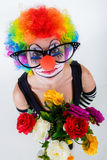 Girl in big black glasses and clown costume with a bouquet of flowers  looks up Stock Photos