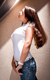 Girl with big breast and long hair leaning against wall outdoor Royalty Free Stock Photos