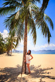 Girl with big bust in white frock leans on big palm on beach Royalty Free Stock Images