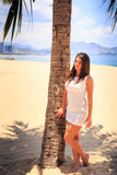 girl with big bust in white frock poses by palm on beach Royalty Free Stock Photo