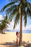 girl with big bust in white leans on palm against row of palms Royalty Free Stock Photography
