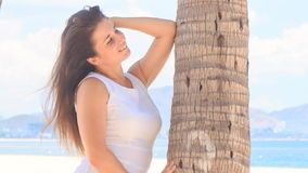Girl with big bust in white leans on palm trunk with elbow stock footage