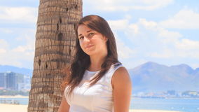 Girl with big bust in white smiles by palm trunk on beach stock footage