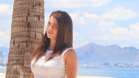 Girl with big bust in white smiles by palm trunk on beach stock video footage