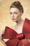 Girl with big christmas bow. Close-up portrait of christmas woman with elegant hair-style taking big glitter bow on her breast Royalty Free Stock Photography