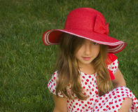 Girl With Big, Floppy Red Hat. A shy little girl with long brown hair partially covering one eye, sits on the green grass wearing a red and white polka dotted stock image