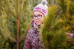 Girl with big glasses and gray and purple hat looking at green christmas tree stock images