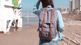 Girl with grey backpack walks on a beach. Close-up. Hair blowing in wind. Coast guard post and houses. Slow motion. Girl with big grey backpack walks on a beach stock video