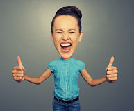 Girl with big head and big thumbs up. Happy screaming girl with big head and big thumbs up royalty free stock images