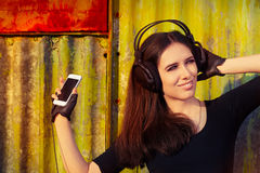 Girl with Big Headphones and Smart Phone on Grunge Background Stock Image