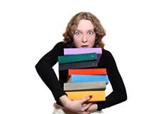 Girl with a big heap of books. Girl holding big heavy heap of multicolored books Royalty Free Stock Photo