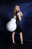 Girl with the big lamp. On dark background royalty free stock photos
