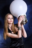 Girl with the big lamp. On dark background royalty free stock photo