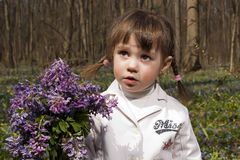 A girl with the big lilac bunch. A girl standing with the big lilac bunch in the forest Stock Images